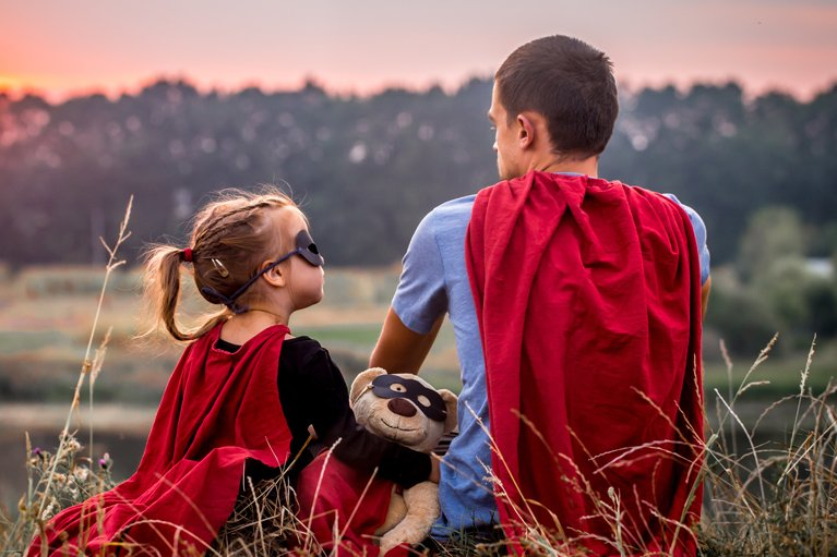 Man and child in red capes to represent who their heroes are and how to protect them with PPE
